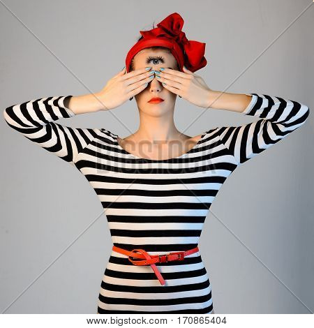 Beautiful Girl In A Striped Dress And A Red Turban On Her Head Is Covering His Eyes With Hands And L