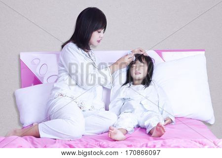 Portrait of young mother checks temperature her girl while looking the thermometer