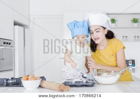 Portrait of young mother and her child making cake together while standing in the kitchen