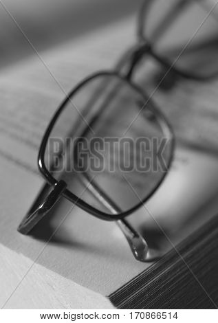 Black and white spectacles on book page