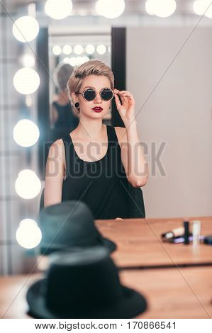 Vertical portrait of young woman with makeup getting ready for going out. Stylish girl in sunglasses sitting at mirror