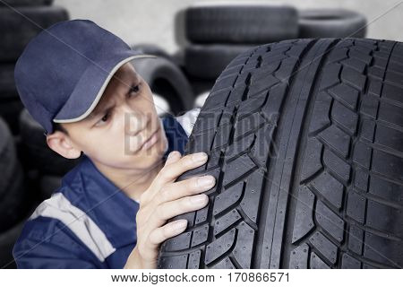 Young mechanic with blue uniform checking black tyre while looking at texture of tyre