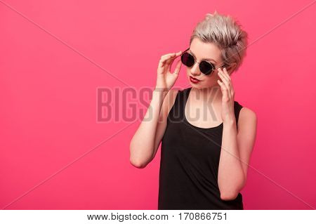 Fashion girl in black shirt and sunglasses on pink background with copy space. Young hipster woman with Blond short dyed hair isolated