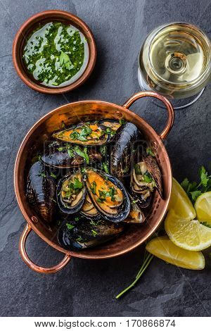 Shellfish Mussels in copper bowl with lemon and herbs sauce. Top view