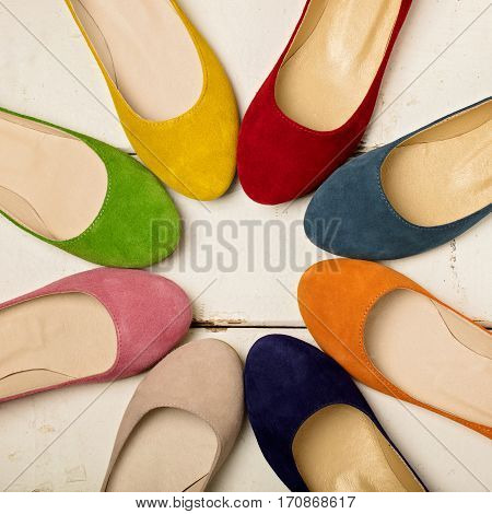 Row of colorful shoes (ballerinas) on a white wooden background. Selective focus.