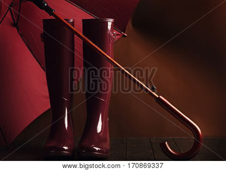 Photo in low key. Rubber boots and umbrella burgundy color on a brown background. Selective focus.