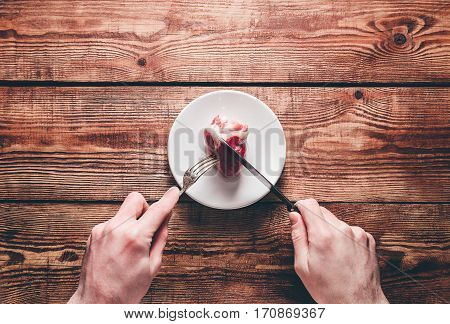 Heart on Plate. Two Hands Cut Heart with Silverware