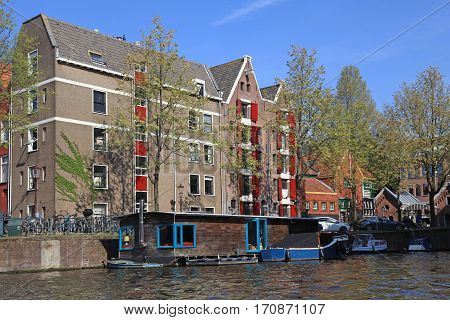 Traditional dutch buldings and houseboat along canal, Amsterdam, Netherlands.