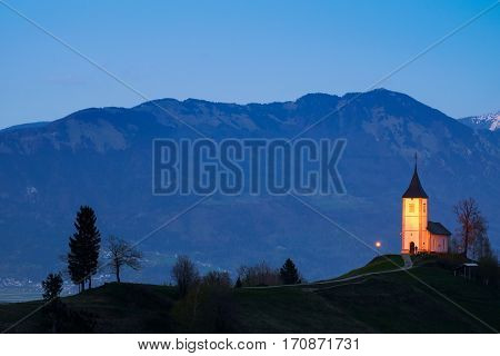 Lonely church on the hill at sunset at Jamnik Slovenia
