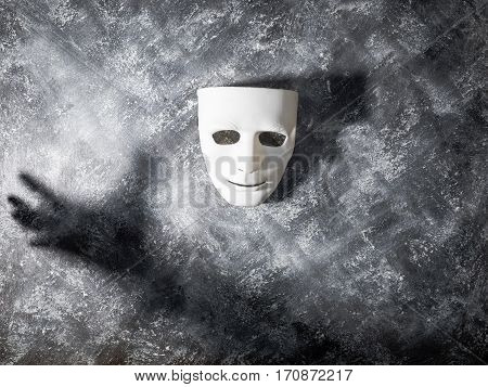 White mask with shadow of hand on gray grunge background.