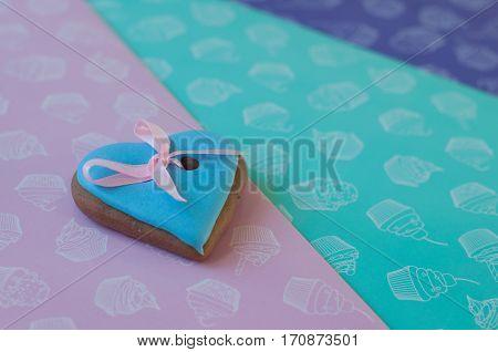 Blue heart shaped glazed honey cake with rose ribbon lay on colorful background