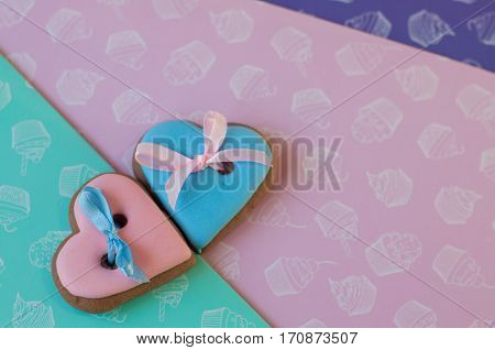 Two hearts made of blue and rose glazed honey cakes with ribbons lay on rose green purple background. Top view. Focus on rose heart