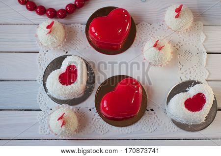 Composition of holiday cakes. Red white cakes and balls lay on wooden table. Top view