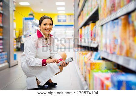 Female sales clerk working at the supermarket