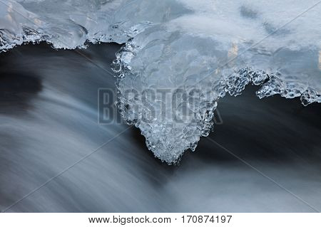 Water and ice in winter mountain stream. Cold icing shapes.