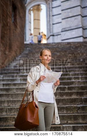 Gorgeous female tourist with a map discovering a foreign city (shallow DOF; color toned image)