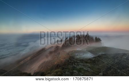 Top of Hill in Fog with View over Frosty Countryside Fields in UK