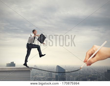 Businessman poised helped by a hand that draws a rope. Help in your business career
