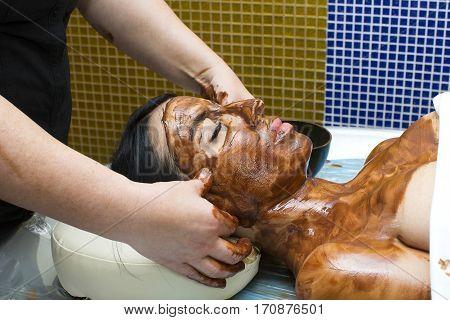Process chocolate mask Woman in a beauty salon