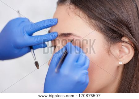 Professional stylist in gloves plucking eyebrows for female client in a beauty salon. Making permanent make up for woman and procedure with brush and forceps. Side view.