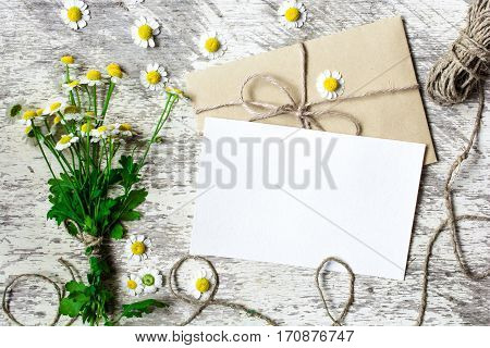 Blank white greeting card and envelope with chamomile flowers and rope mockup on white rustic wood background for creative work design. top view