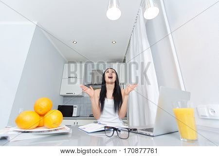 Brunette woman in white top, with long hair rising up and happy shouting. Happy woman holding hands up, finishing home task and having new idea. Modern interior of kitchen with fruits on table.