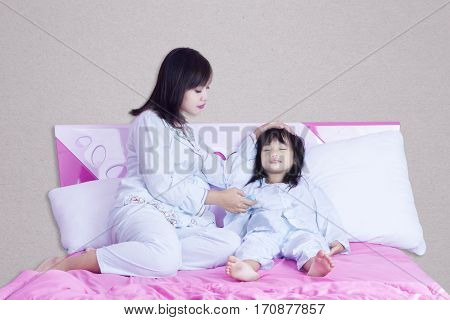 Portrait of young mother checks temperature her sick child with thermometer on the bed