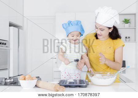 Portrait of young mother and little daughter making cake together while sitting in the kitchen
