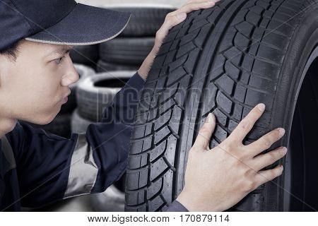 Mechanic with uniform controlling black tyre while looking at texture of tyre