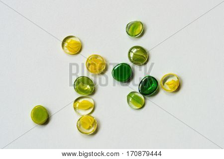 Green and yellow decorative glass stones close-up on light surface. For beautiful abstract modern background pattern wallpaper or banner design