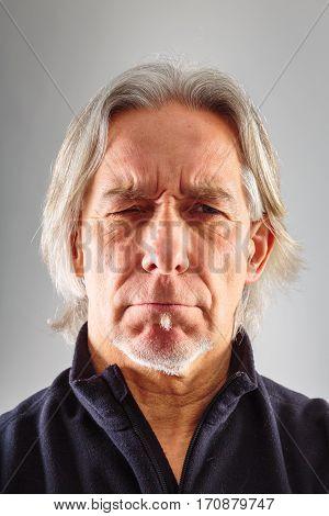 senior man's portrait, taken in studio on grey background.