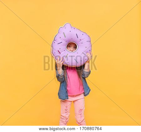 Portrait of a girl looking through zero. Little child holding a big sweet donut over colorful background