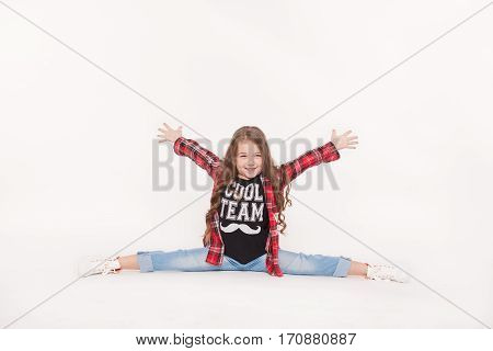 Happy Little girl with hands up sitting on twine isolated on white. Cute child smiling in the splits. Dance school