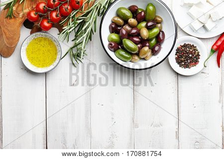 Fresh olives, feta cheese, cherry tomatoes, chili, rosemary, garlic, peppercorns and olive oil on white wooden background