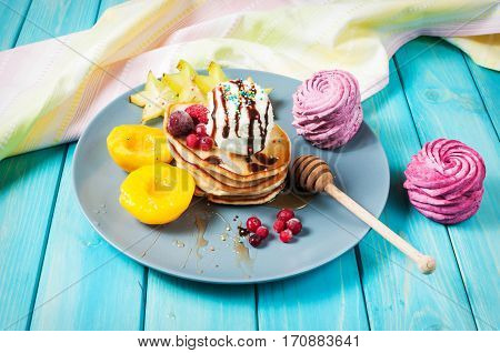 Pancakes with Vanilla Ice Cream on blue wood plate.