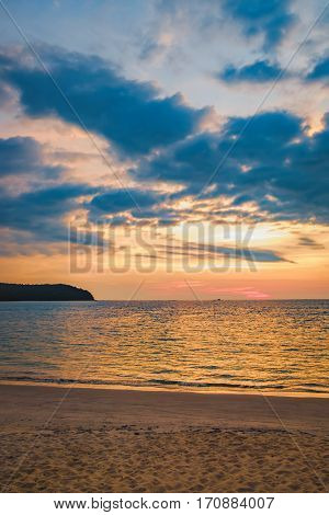 Coast of the sea at colorful sunset at Pantai Tengah Beach, Langkawi island, Malaysia. Golden sunset sky with a wave rolling to shore as the sun sets over the water horizon