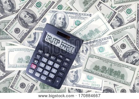 Piles of dollar currency with Trump Effect word on the calculator screen