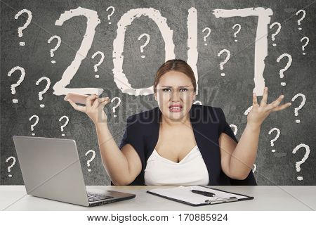 Confused woman sitting with number 2017 on the wall while shrugs her shoulder as her doubt expression