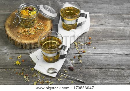 Two glass cups of herbal tea. Glass jar on the board with dry herbal tea. Herbal tea is scattered on gray vintage wooden board. Blank space.