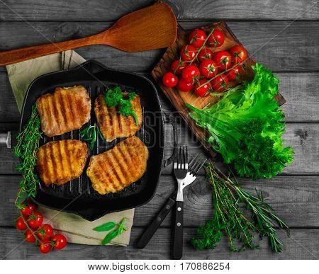 Pieces grilled pork steaks on frying grill pan rustic wooden gray table. Ingredients for meat pork steaks grilled tomatoes parsley thyme rosemary. Beside special scapula for meat. Top view.