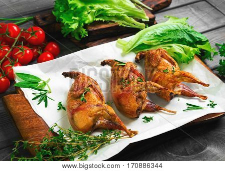 Roasted quail on a wooden tray. Spice for roasted quail - thyme rosemary lettuce parsley and cherry tomatoes. Gray wooden background.