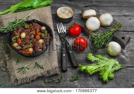 Cooking meat on Burgundy. Stew meat in Burgundy in in cast iron frying pan with carrots onions. Spices for meat Burgundy thyme cherry tomatoes mushrooms champignons. Gray wooden background.
