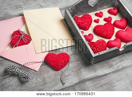 Card to Valentine's Day. Paper for text congratulations letter. Heart from red marzipan in box. Heart with pattern and heart sleek white wooden background.