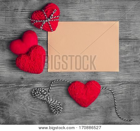 Card to Valentine's Day. Paper for text congratulations letter. Heart from red marzipan. Heart with pattern and heart sleek white wooden background.Top view.