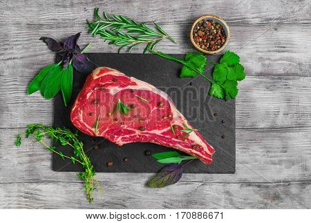 Raw fresh cow meat rib eye steak on the black stone board. Seasoning for meat rib eye steak thyme basil sage rosemary coriander pepper. Light white wooden background. Top view flat lay.