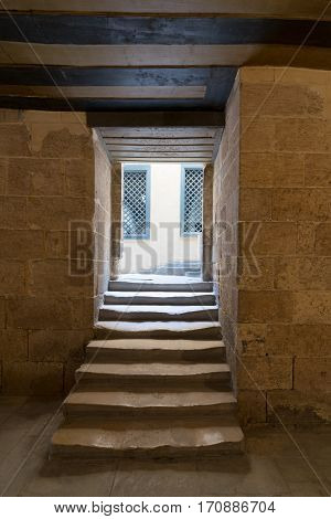 Aged narrow dark vaulted passage and staircase leading to outdoor small lobby with two yellow wooden windows, Medieval Cairo, Egypt