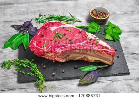Raw fresh cow meat rib eye steak on the black stone board. Seasoning for meat rib eye steak thyme basil sage rosemary coriander pepper. Light white wooden background.