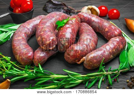 Raw uncooked meat sausages on a black cutting board. Spices for raw meat sausages onions garlic thyme rosemary sage leaves cilantro peppers cherry tomatoes. Dark rustic wooden background.