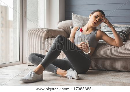 Attractive slim girl in sportswear is feeling tired and exhausted holding a bottle of water while sitting on the floor at home