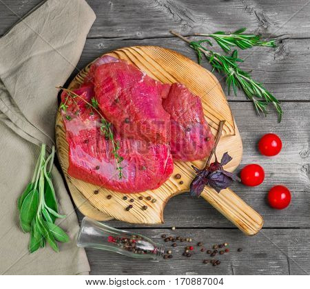 Fresh raw beef meat. Whole pieces of red meat ready to cooking of grill BBQ on cutting board on gray wooden background. Spices for flesh meat beef rosemary thyme sage pepper tomatoes basil. Top view.